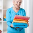 Elderly lady folding towels — Stock Photo