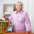 Senior lady during folding laundry — Stock Photo