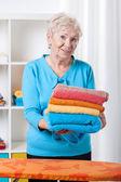 ältere dame, die handtücher falten — Stockfoto