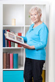Elderly woman looking through photo album — Stock Photo