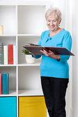 Senior lady viewing family album — Stock Photo