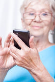 Senior lady using cellular phone application — Stock Photo