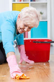 Senior woman washing floor — Stock Photo