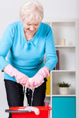 Elderly lady wringing cloth — Stock Photo