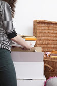 Woman packing books — Stock Photo