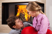 Smiling couple by fireplace — Stock Photo