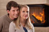 Young couple by fireplace — Stock Photo