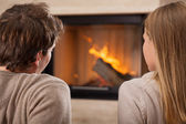 Sitting by fireplace — Stock Photo