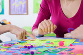 Teacher playing colourful puzzles with kids — Stok fotoğraf