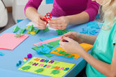 Little girl making crafts with teacher — Stock Photo