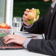 Worker eating at his desk — Stock Photo