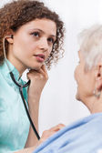Nurse examining elderly lady — Stock Photo