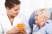 Nurse taking care of elderly woman — Stock Photo