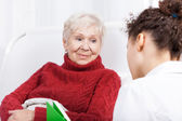Elderly lady listening to nurse — Stock Photo