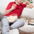 Couch potato eating junk food — Stock Photo