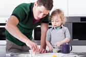 Father baking cookies with son — Stok fotoğraf