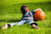 Boy laid down on the grass — Stock Photo