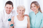 Physiotherapists and exercising elderly woman — Stock Photo