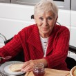 Disabled elderly in kitchen — Stock Photo