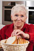 Elderly woman taking bread — Stock Photo
