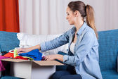 Lady packing clothes into box — Stock Photo