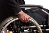 Male hand on wheel of wheelchair — Stock Photo