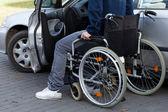 Man in wheelchair next to car — Stock Photo