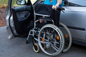 Man packing wheelchair into a car — Stock Photo