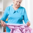 Elderly woman preparing shirt to ironing — Stock Photo