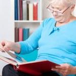 Elderly woman watching photos — Stock Photo #45717753