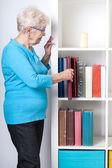 Elderly woman taking off photo album from shelf — Stockfoto