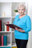 Senior woman viewing photo album — Stockfoto