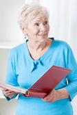 Elderly woman with photo album — Stockfoto