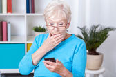 Elderly woman surprised by text message — Stock Photo