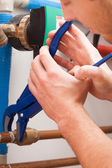 Repairman with pipe wrench — Stockfoto