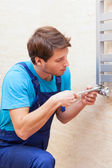 Young repairman fixing heater — Stock Photo