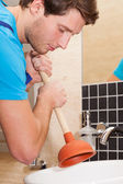Handyman using plunger — Stockfoto