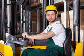 Storehouse employee driving on forklift — Stock Photo
