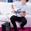 Boy playing electric guitar in his room — Stock Photo #46375091