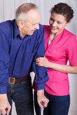 Man on crutches and his nurse — Stockfoto