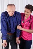 Медсестра защиты человек на костылях — Стоковое фото