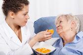 Nurse feeding elderly woman — 图库照片