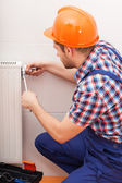 Repairman fixing radiator — Stock Photo