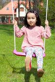 Asian girl swinging — Stock Photo