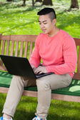 Asian man using laptop — Stock Photo