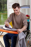 Happy disabled man during ironing — Stock Photo