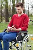 Disabled reading a book in garden — Stock Photo