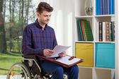 Disabled man viewing documents — Stockfoto