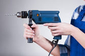 Woman holding a drill — Stockfoto