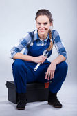 Woman sitting on toolbox — Stockfoto